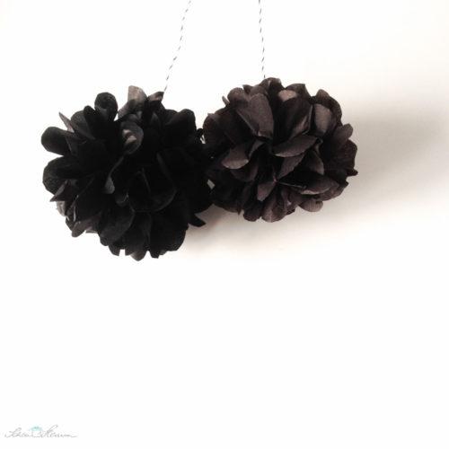 Schwarze Pompons.