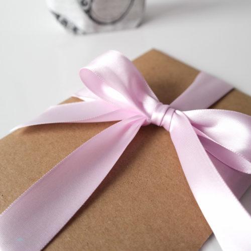 Kraftpapierumschlag zur Hochzeit mit rosa Schleife aus Satinband. Schönherum