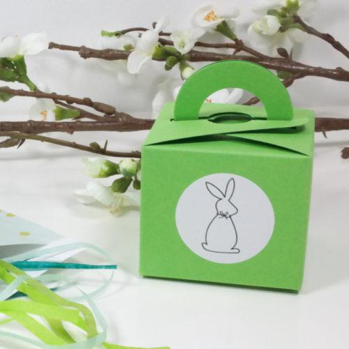 grüne Geschenkschachtel mit Henkel und Hasenaufkleber