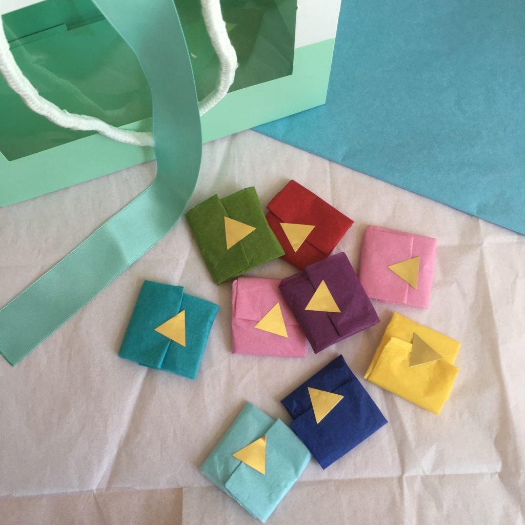 Geldgeschenk basteln - Geld einfach quadratisch falten und in verschieden farbige Seidenpapierstücke einschlagen. Zum Verschluss einen hübschen Aufkleber verwenden.
