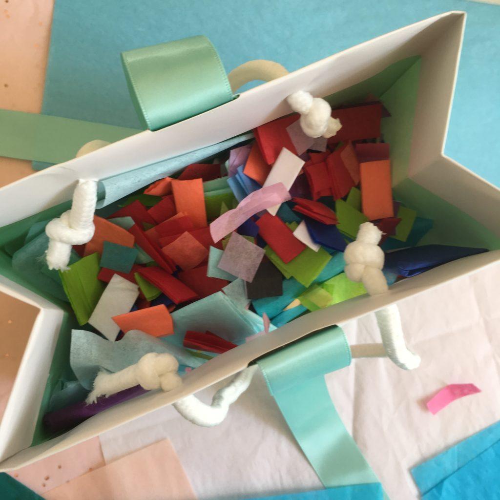 Geldgeschenk basteln - Seidenpapier Konfetti in eine Geschenktasche füllen.